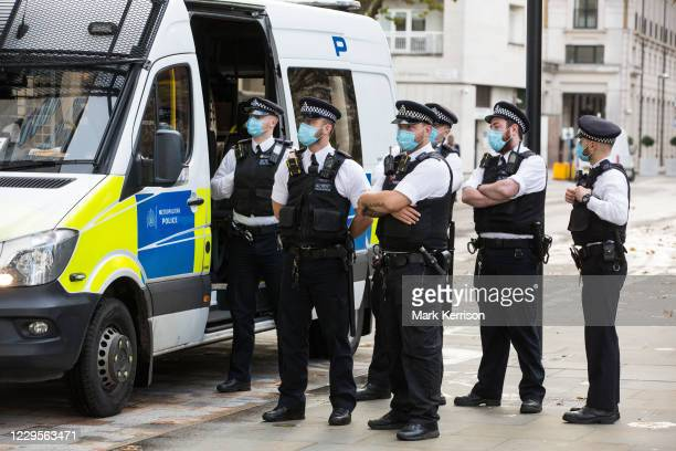 Metropolitan Police officers wearing face coverings prepare to speak to environmental activists from Extinction Rebellion protesting outside the...