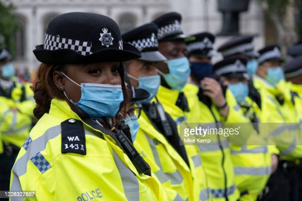 Metropolitan police wearing face masks form a cordon at Extinction Rebellion demonstration on 3rd September 2020 in London, United Kingdom. With...