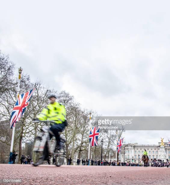 バッキンガム宮殿の近くをさまよっている観光客に目を光らせて、モールに沿ってサイクリング高い視認性のジャケットを着た警視庁の警官。低角度、モーションブラーショットは、コピー� - ロンドン ザ・マル ストックフォトと画像