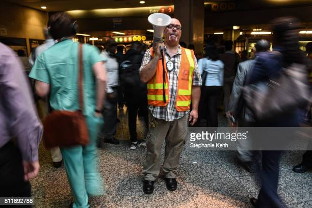 Metropolitan Transit Authority employee helps commuters transfer from Long Island railroad service to a New York City subway at the Barclays Center...