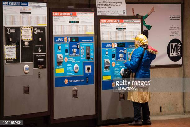 A Metrorail commuter uses a fare machine at a station in Washington DC on October 24 2018 As the US capital traded stifling summer heat for cool...