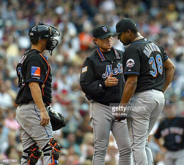 Mets' pitching coach Bobby Floyd tries to calm down pitcher James Baldwin as catcher Jason Phillips listens in during game action at Minute Maid Park...