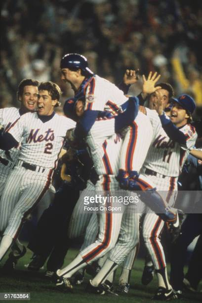 Mets players rush to the field as Gary Carter jumps into the arms of Jesse Orosco after a come behind victory against the Boston Red Sox during the...