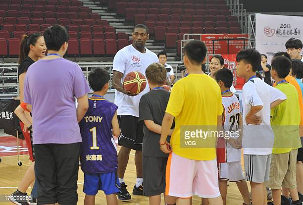 Metta World Peace of Los Angeles Lakers plays basketball with children at MasterCard Center on June 30 2013 in Beijing China