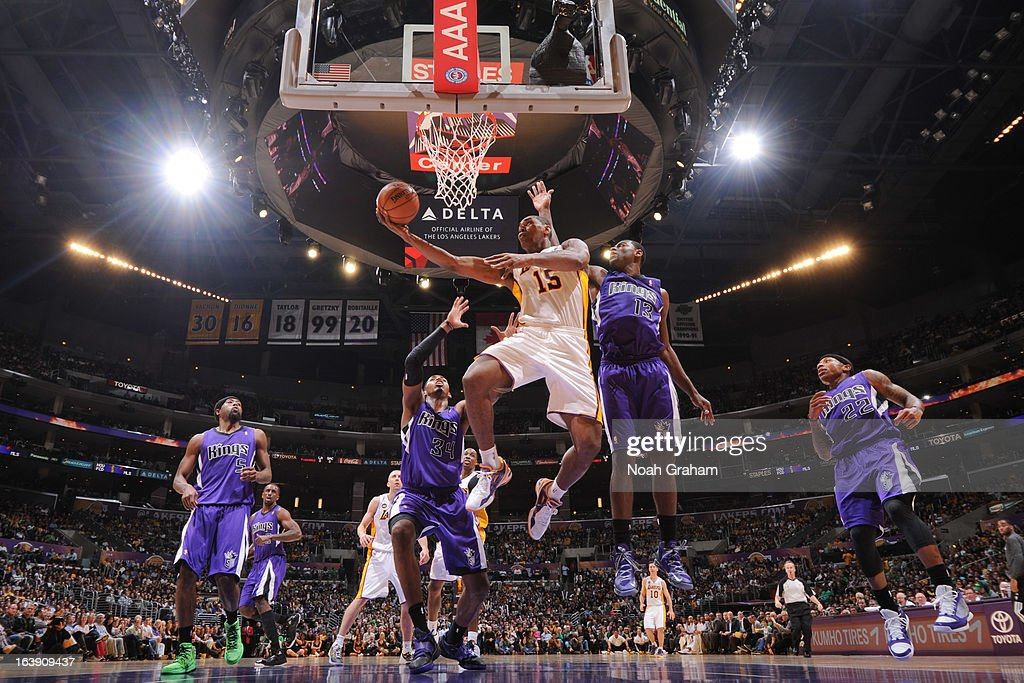 Metta World Peace #15 of the Los Angeles Lakers attempts a layup against Jason Thompson #34 and Tyreke Evans #13 of the Sacramento Kings at Staples Center on March 17, 2013 in Los Angeles, California.