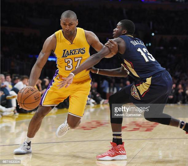 Metta World Peace of the Los Angeles Lakers drives around Cheick Diallo of the New Orleans Pelicans during the second half of the basketball game at...