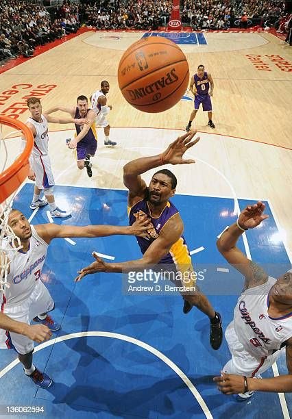 Metta World Peace of the Los Angeles Lakers goes to the basket against Brian Cook and Caron Butler of the Los Angeles Clippers at Staples Center on...