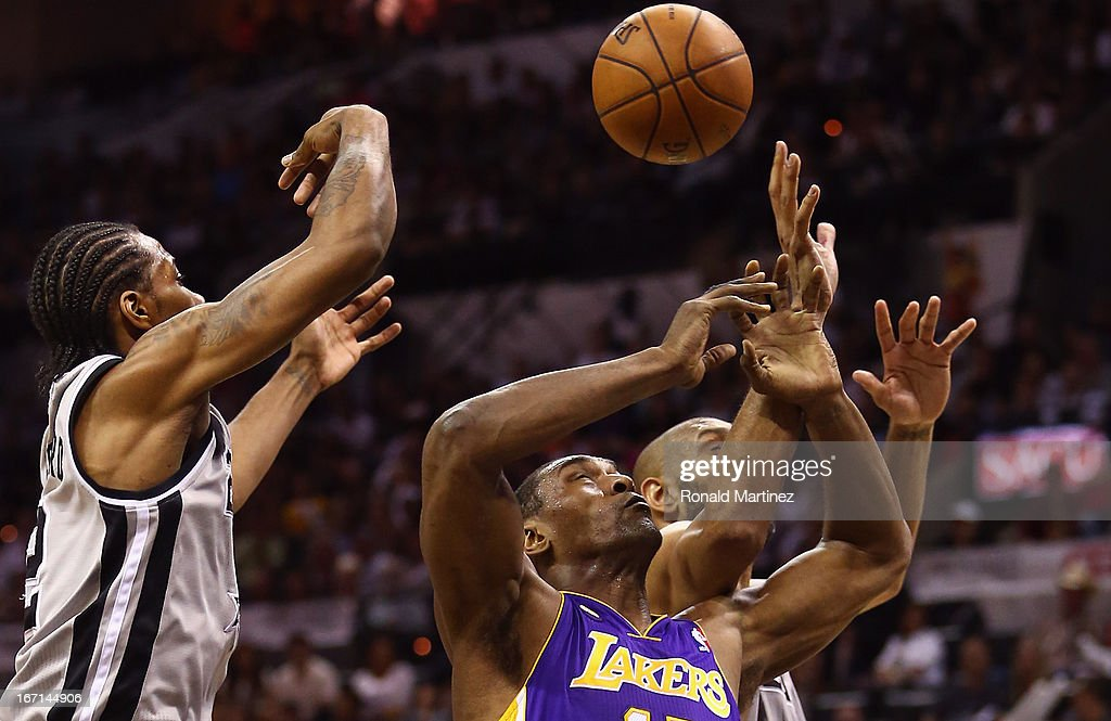 Metta World Peace #15 of the Los Angeles Lakers reaches for a rebound with Kawhi Leonard #2 of the San Antonio Spurs and Tim Duncan #21 of the during Game One of the Western Conference Quarterfinals of the 2013 NBA Playoffs at at AT&T Center on April 21, 2013 in San Antonio, Texas.