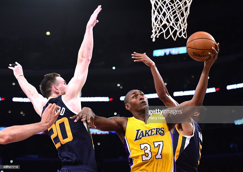 Metta World Peace #37 of the Los Angeles Lakers scores between Gordon Hayward #20 and Rodney Hood #5 of the Utah Jazz during the first half at Staples Center on December 5, 2016 in Los Angeles, California.