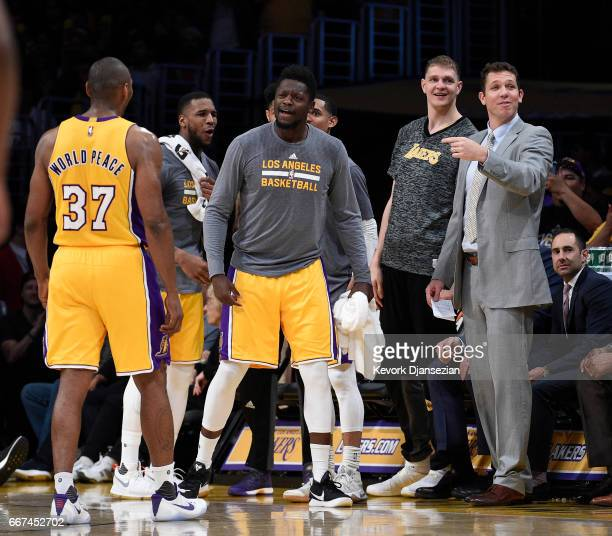 Metta World Peace of the Los Angeles Lakers who ended up scoring a teamhigh 18 points is congratulated by teammate Julius Randle and head coach Luke...