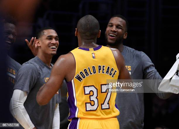 Metta World Peace of the Los Angeles Lakers who ended up scoring a teamhigh 18 points is congratulated by teammates Jordan Clarkson and Thomas...