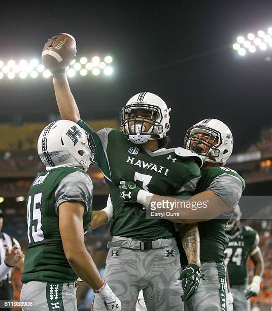 Metuisela `Unga of the Hawai'I Rainbow Warriors holds the football high as he is congratulated by his teammates after making a touchdown reception...