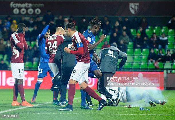 Metz' and Lyon's players react after a firecracker has exploded on the pitch during the French L1 football match between Metz and Lyon on December 3...