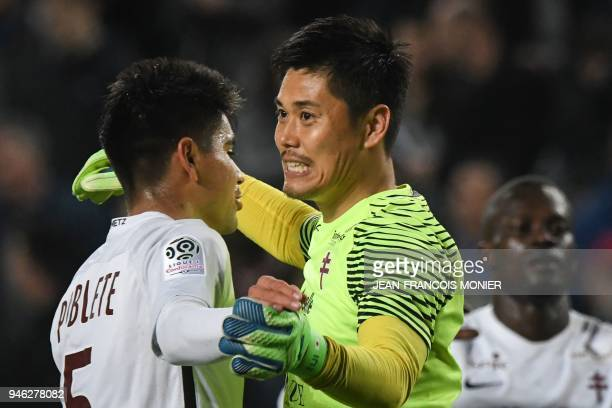 Metz' Argentinian midfielder Geronimo Poblete celebrates with his teammate Japanese goalkeeper Eiji Kawashima at the end of the French L1 Football...