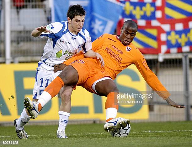 Metz' defender Sebastien Bassong fights for the ball with Auxerre's forward Julien Quercia during the French L1 football match Auxerre vs Metz on 19...