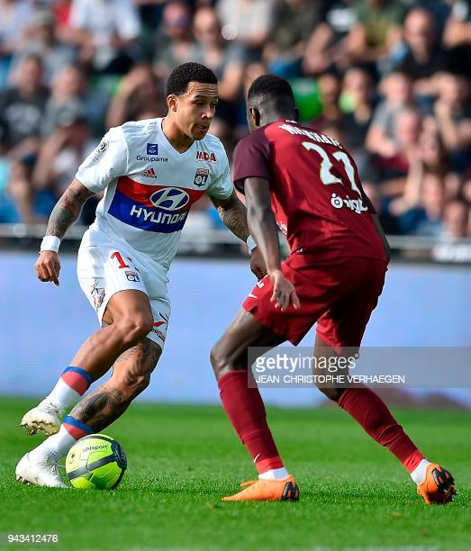 Metz' French defender Moussa Niakhate vies for the ball with Lyon's Dutch forward Memphis Depay during the French L1 football match between Metz and...