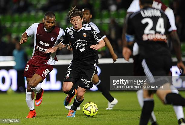 Metz' French midfielder Florent Malouda vies for the ball with Lorient's French midfielder Mehdi MostefaSbaa during the French L1 football match...