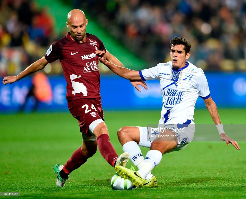 Metz' French midfielder Renaud Cohade (L) vies for the ball with Troyes' French midfielder François Bellugou during the French L1 football match between Metz (FCM) and Troyes (ESTAC) on September 23, 2017 at Saint Symphorien stadium in Longeville-Les-Metz, eastern France. VERHAEGEN