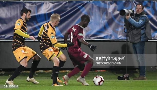 Metz' Gambian forward Ablie Jallow vies with Orleans' French Defender Quentin Lecoeuche and Orleans' French Defender Gauthier Pinaud during the...