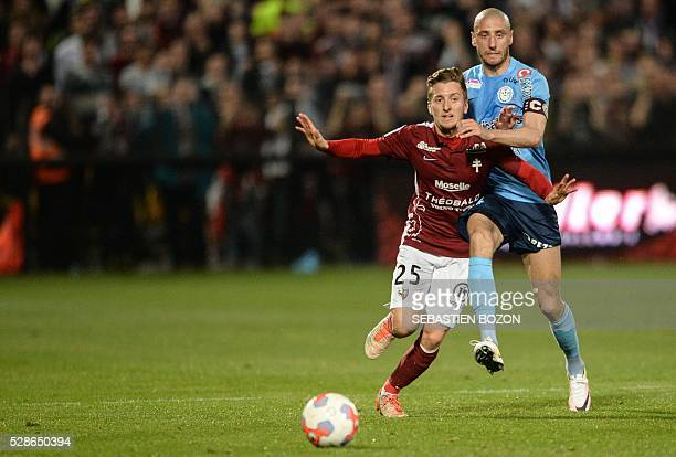 Metz' Spanish defender Ivan Balliu vies for the ball with Tours' French midfielder Laurent Agouazi during the French L2 football match between Metz...