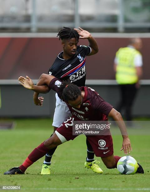 Metz's French defender Benoit AssouEkotto vies for the ball with Crystal Palace's BelgianCongolese midfielder Jason Lokilo during a friendly football...