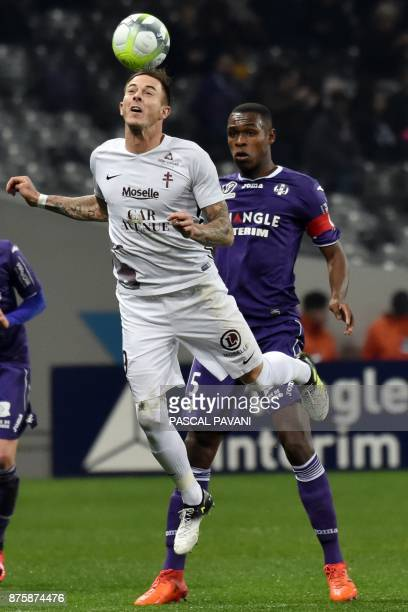 Metz's French forward Nolan Roux heads the ball as he vies with Toulouse's French defender Issa Diop during the French L1 football match between...