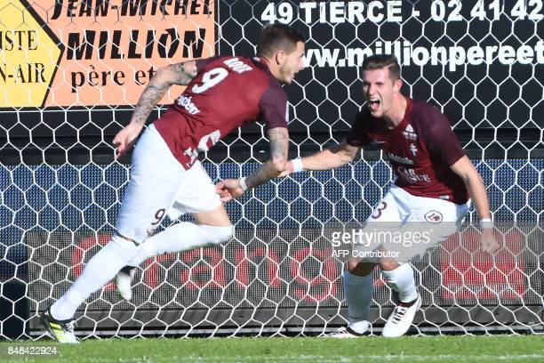 Metz's French forward Nolan Roux is congratulated by Metz's Luxemburg defender Chris Philipps after scoring Angers' French goalkeeper Alexandre...