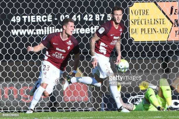 Metz's French forward Nolan Roux is congratulated by Metz's Luxemburg defender Chris Philipps after scoring in spite of Angers' French goalkeeper...