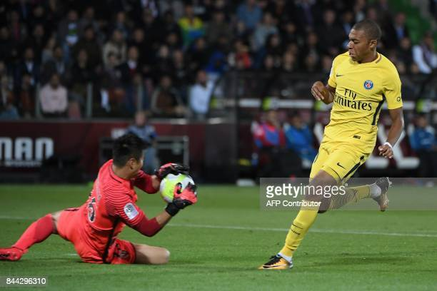 Metz's Japanese goalkeeper Eiji Kawashima blocks the ball as Paris SaintGermain's French forward Kylian Mbappe looks on during the French L1 football...