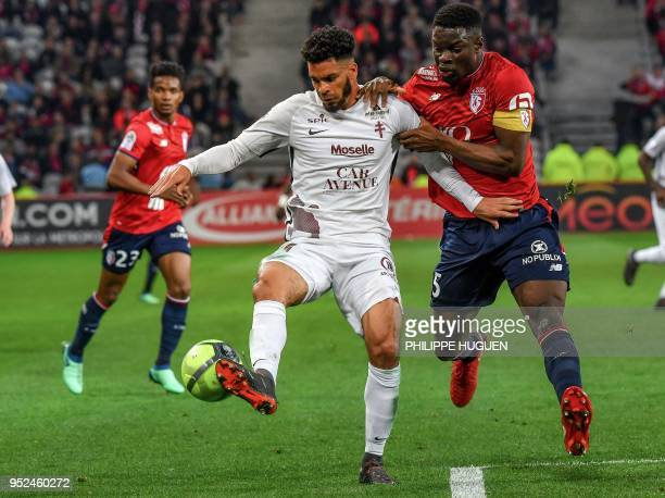 Metz's Luxembourg midfielder Vincent Thill vies with Lille's French defender Adama Soumaoro during the French L1 football match between Lille and...