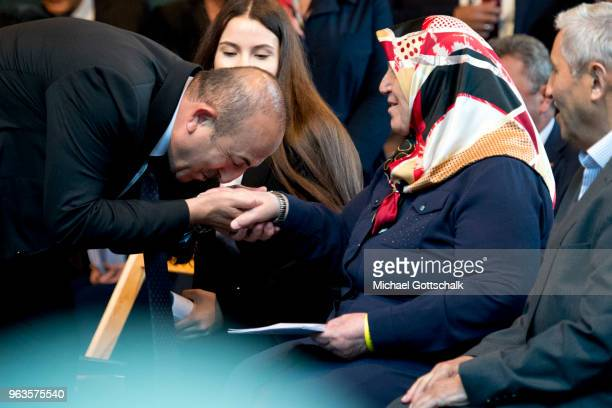 Mevlut Cavusoglu Foreign Minister of Turkey kisses the hand of Mevlude Genc during the commemoration of the arson attack on the house of the Turkish...