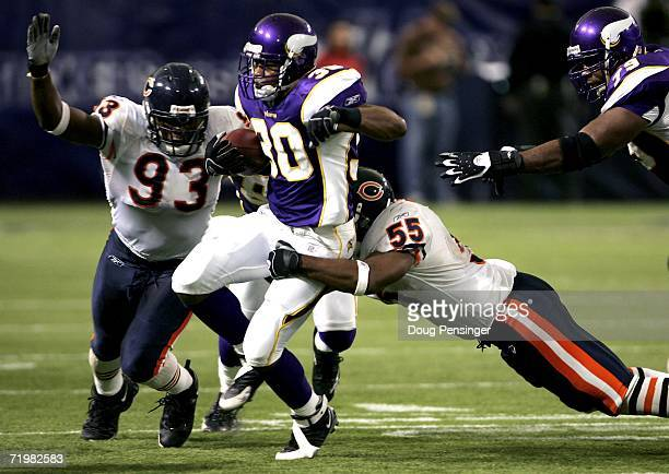 Mewelde Moore of the Minnesota Vikings is brought down by Lance Briggs and Adewale Ogunleye of the Chicago Bears on September 24 2006 at the...