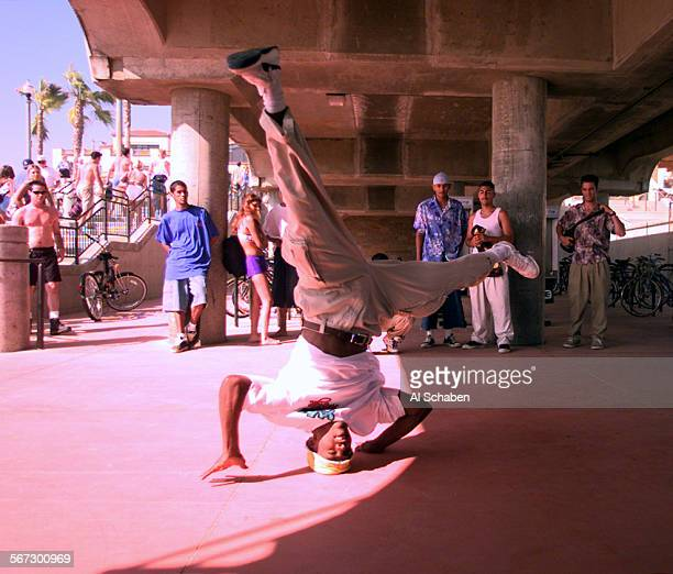 MEwildartbreak20705AS––HUNTINGTON BEACH––Jeremy 'Silhouette' Washington of San Bernadino performs a headspin breakdance move before a crowd under the...