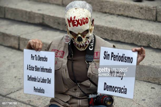 TOPSHOT Journalists hold signs during a protest against the recent murder of the correspondent journalist Miroslava Breach of La Jornada newspaper at...