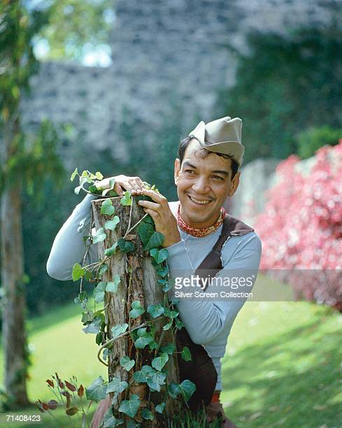 Mexican actor and comedian Cantinflas born Mario Moreno Reyes looking Puckish behind an ivycovered stump circa 1950