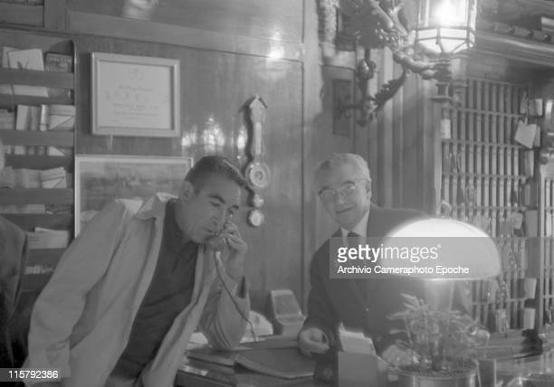 Mexican actor Anthony Quinn resting on his elbow on the hotel front desk speaking on the telephone the receptionist behind him Lido Venice 1959