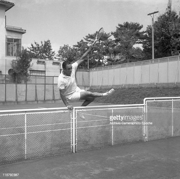 Mexican actor Anthony Quinn wearing tennis clothes a Fred Perry tshirt jumping over the tennis court fence with a racket on his hand Lido Venice 1960s