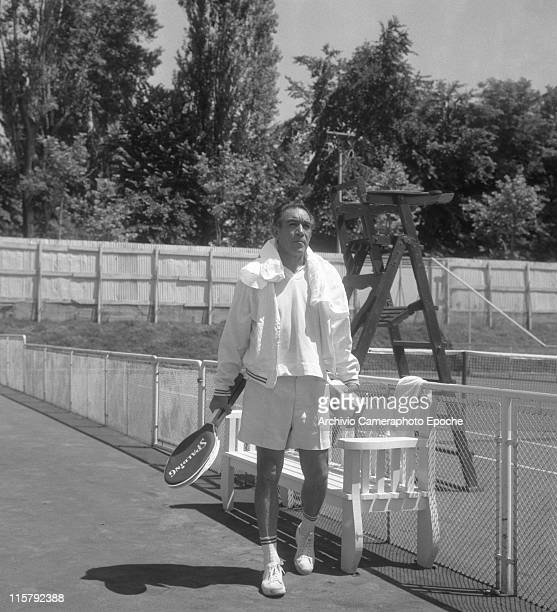 Mexican actor Anthony Quinn wearing tennis clothes a towel on his shoulders and holding a Spalding racket and balls boxes standing beside the tennis...