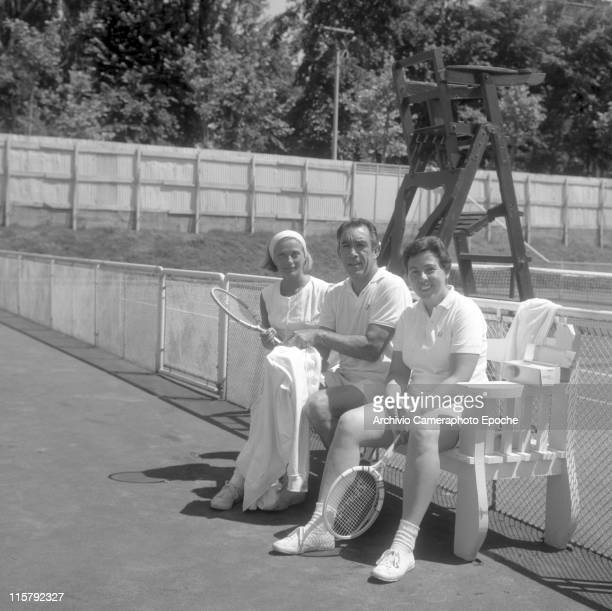 Mexican actor Anthony Quinn wearing tennis clothes sitting on a bench with two women one with a tennis racket beside the tennis court an umpire chair...