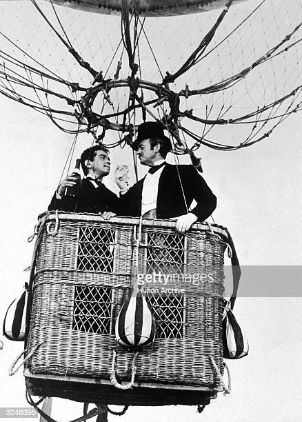 Mexican actor Cantinflas and British actor David Niven toast with champagne while riding in a hot air balloon basket in a still from the film 'Around...
