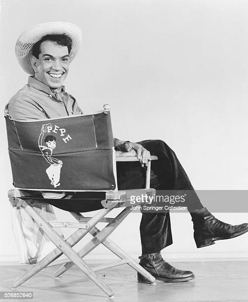 Mexican actor Cantinflas relaxes in a directors' chair