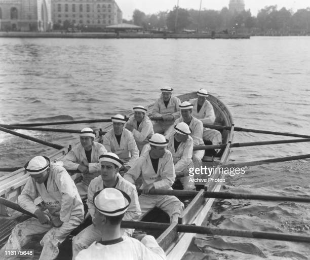 Mexican actor Ramon Novarro in the foreground with a group of rowers in a still from the 1925 film 'The Midshipman'