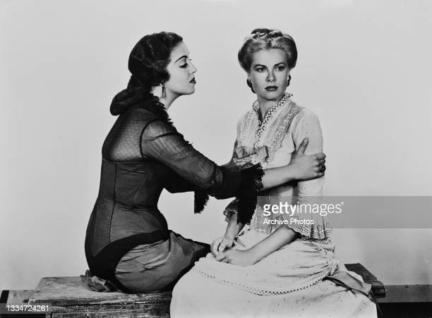 Mexican actress Katy Jurado consoling American actress Grace Kelly , who looks away, in a publicity image for 'High Noon, location unspecified, 1952....