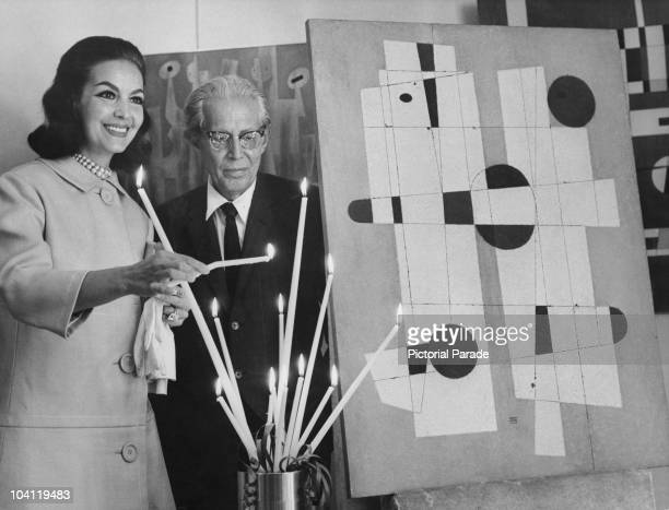 Mexican actress Maria Felix lights candles at a private view of work by Guatemalan artist Carlos Merida at the Reichenbach Gallery Paris 19th June...