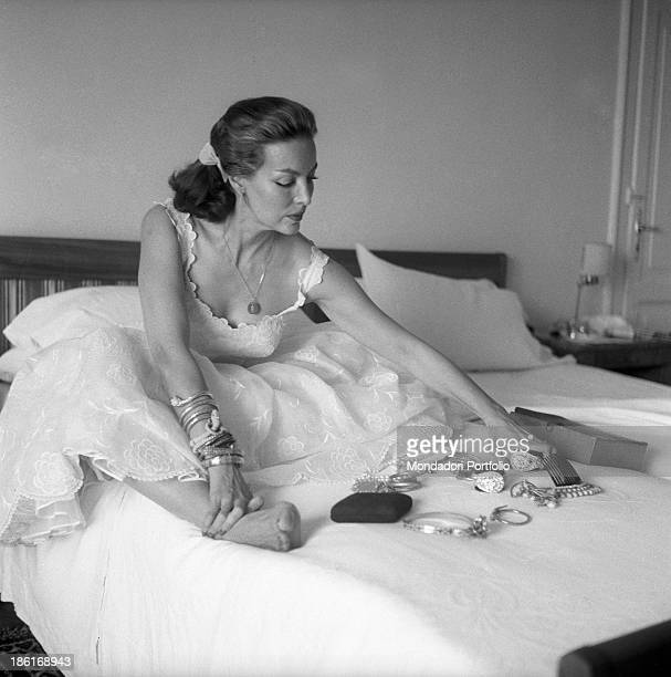Mexican actress Maria Félix showing her jewels seated on the bed of a hotel room She's taking part in the Venice Film Festival Venice August 1959