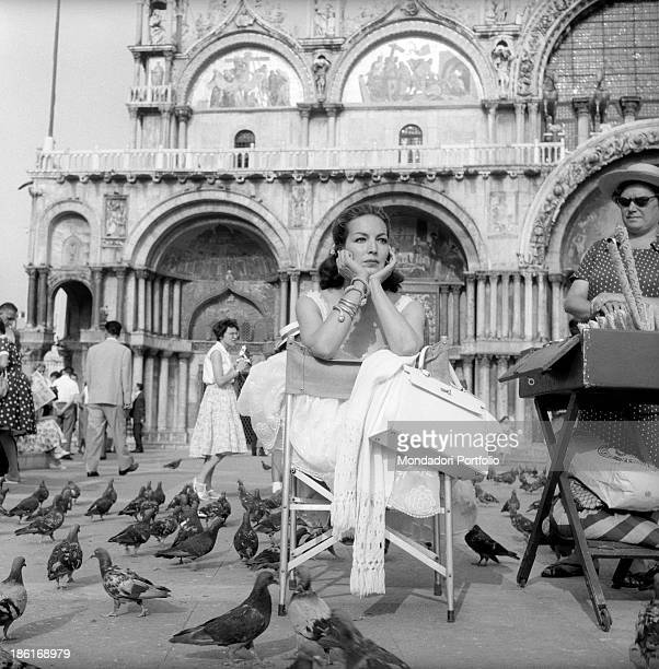 Mexican actress Maria Félix sitting on a folding chair in Piazza San Marco surrounded by the pigeons She's taking part in the Venice Film Festival...