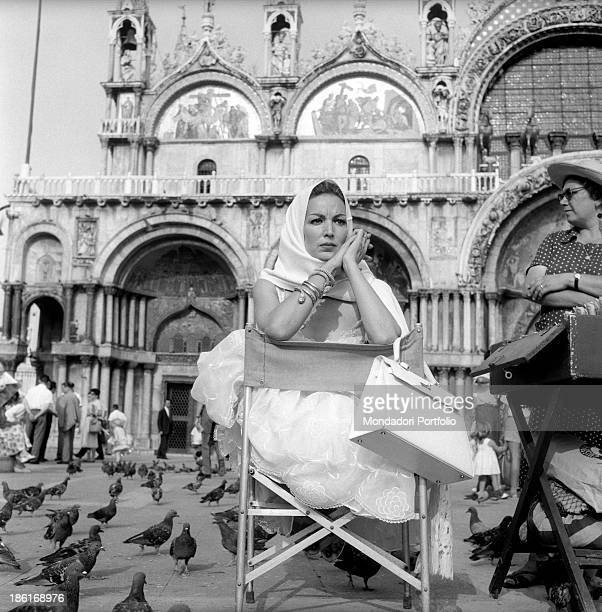 Mexican actress Maria Félix with a scarf around her head sitting on a folding chair in Piazza San Marco surrounded by the pigeons She's taking part...