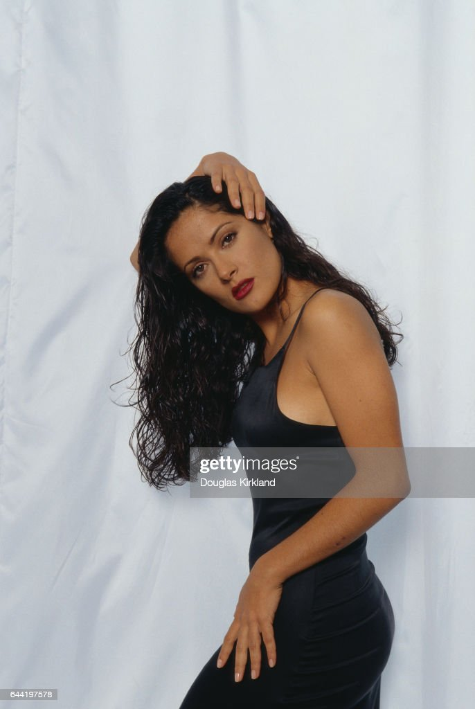 Mexican actress Salma Hayek poses with her hand on her head.