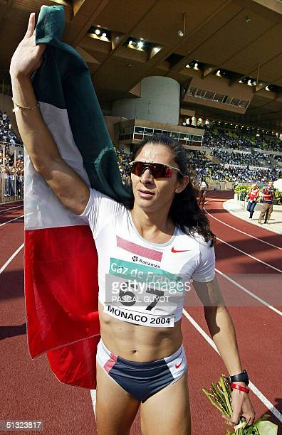 Mexican Ana Guevara holds her national flag after winning the 400m race of the IAAF 'World Athletics Finals' 19 September 2004 at the Louis II...