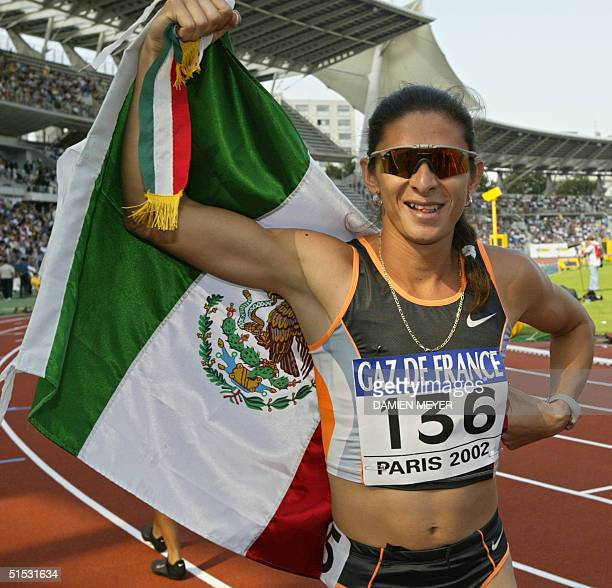 Mexican Ana Guevara jubilates with her national flag after winning the women's 400m race in 4990 14 September 2002 during the IAAF GrandPrix Final in...